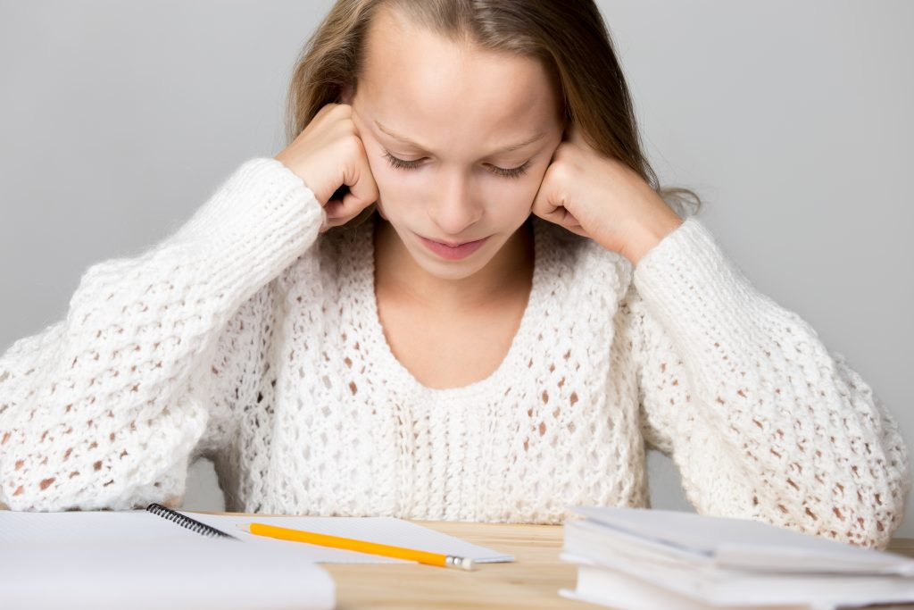 Portrait of stressed beautiful casual girl, sitting at desk, holding her head in arms with exhausted frustrated expression, cannot understand hard school task, studio, gray background problèmes practical